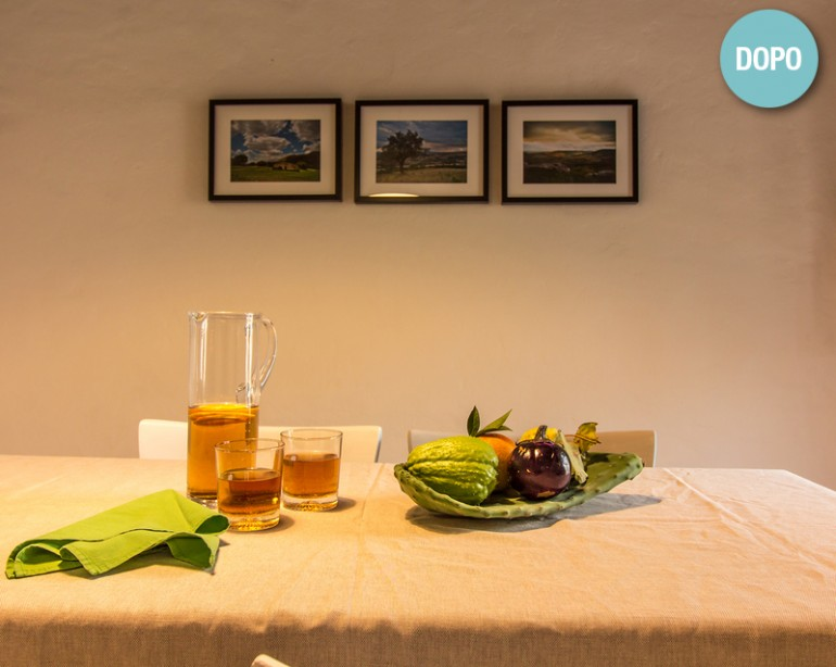 Il tavolo accoglie coi frutti della Sicilia; foto d'autore dei dintorni sulla parete